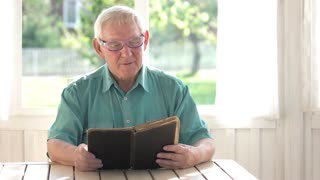 Senior man reading a book. Thoughtful person in glasses. Learning program for seniors.