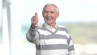 Senior man showing thumb up. Happy grandfather giving thumb up, blurred background. Human emotions and gestures.