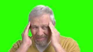 Senior man suffering from migraine, green screen. Elderly man having terrible headache, alpha channel background.