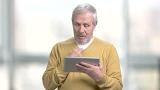 Senior man talking via internet. Elderly smiling man using digital tablet on blurred background. Older people and technology.