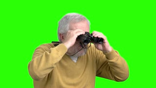 Senior man with binoculars, green screen. Old man in yellow sweater looking through binoculars, chroma key background. Expedition and exploration concept.