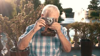Senior man with camera. Elderly male outdoor. Grandpa found a new hobby. Impressive photos of nature.