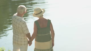 Senior people standing near water. Elderly couple kissing near river in sunny day. Family happiness and romance.