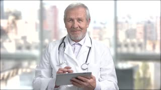 Senior smiling doctor with pc tablet. Elderly bearded doctor working on his tablet at work. People, technology, connection.