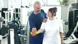 Senior woman at gym lifting dumbbell. Elderly woman lifting dumbbell with her husband at gym. Sport and healthy lifestyle.