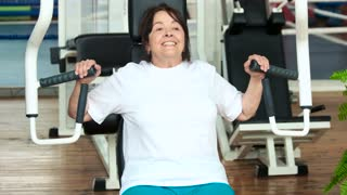 Senior woman doing press push weight exercise. Retired woman training at modern gym. Stay healthy with regular workouts.