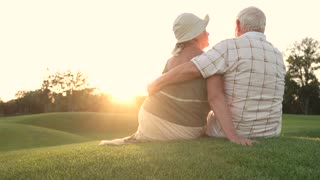 Senior woman kissing her man outdoors. Romance between elderly couple, back view. Man and woman outdoor. Give me a kiss.