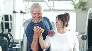 Senior woman lifting dumbbell at gym. Elderly trainer helping to woman lifting dumbbell at fitness club. Happy sporty seniors.