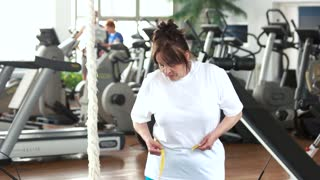 Senior woman measuring her waist at gym. Elderly woman expressing success after measuring herself with tape at fitness club. Weight loss after sport training.