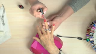 Senior woman receiving manicure in nail salon. Manicure specialist applying red varnish on elderly woman nails in professional nail studio, top view.