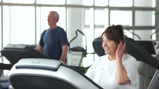 Senior woman running on treadmill. Smiling elderly female training at gym and listening to music. Always be in shape.