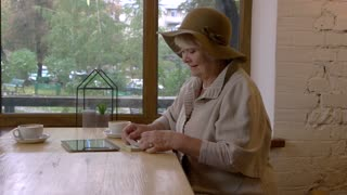 Senior woman with a tablet. Money on the table. Find ways to decrease taxes.