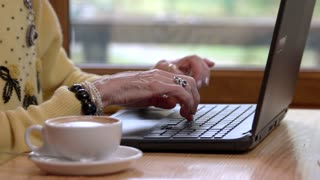 Senior woman's hands and keyboard. Notebook pc and cup. Learn to type fast.