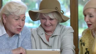 Senior women with tablet smiling. Three cheerful ladies.