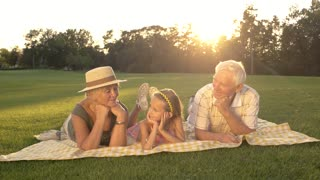 Seniors and granddaughter having rest in park. Happy people outdoors. Taking care of grandchildren.