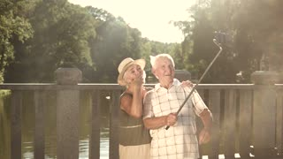 Seniors taking a video with selfie stick. Cheerful couple of elderly people posing and smiling, holding monopod on beautiful nature background.
