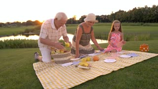 Seniors with granddaughter, nature. Elderly people placing fruits on picnic cloth. Grandparents with child on picnic. Happy time on fresh air.