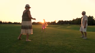 Seniors with granddaughter on green meadow. Slow motion grandparents with their grandchild playing sport game with ball on fresh air, summer sunset. Happy family weekend and relax.