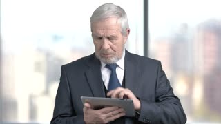 Serious bearded businessman working on pc tablet. Elderly boss in business suit using tablet in office. People, buiness, finance.