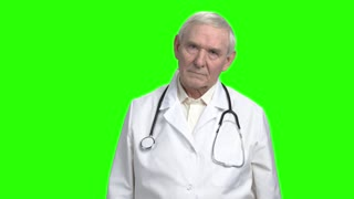 Serious grave earnest doctor. Portrait of frowning old doctor touching his face, green hromakey background for keying.