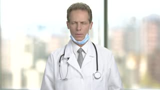 Serious mature doctor, blurred background. Troubled male doctor adjusting his stethoscope. Bad news after patient examination.