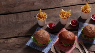 Set of burgers with fries. Cutlery and hamburgers on table. Burgers on old wooden background. Best burgers at retro diner.