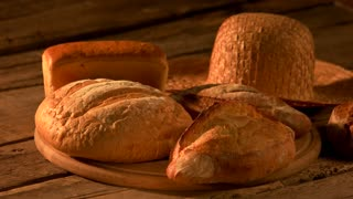 Set of freshly baked bread on rustic background. Fresh healthy bread and straw hat on vintage wooden background. Still life homemade organic pastry.