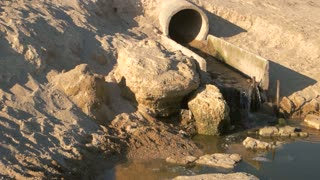 Sewage pipe near the seashore. Dark dirty water. Pollution of the sea.