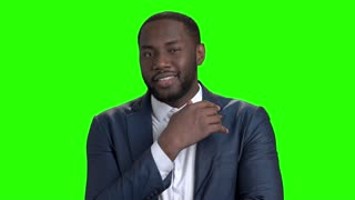Sexy afro american man on green screen. Portrait of a flirting african american man winking with eye on chroma key background. Young flirtatious businessman.