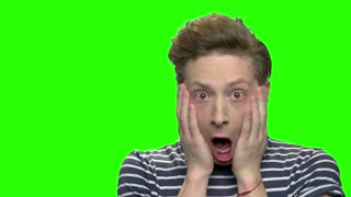Shocked and surprised teenage boy. Touching cheeks. Green screen hromakey background for keying.