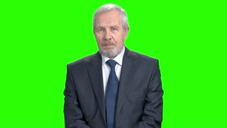 Shocked elderly businessman, green screen. Senior businessman holding his head in shock and surprise, chroma key background. Anxiety and trouble concept.
