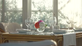Side view of dining table. Flower vase and tableware.