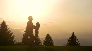 Silhouette of father holding little baby in his hands on sunset. Throwing up a child in the evening.