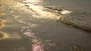Silhouette of woman running, seashore. Sparkling waves in slow-mo.