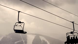 Silhouettes of skiers in a chairlift on sky background