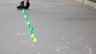 Skater go round chips on rollers. Close up. Professional skate roller making tricks.