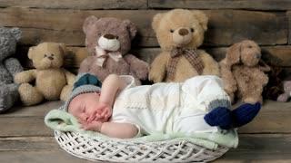Sleeping baby and teddybears. Basket with child on wood. How long should children sleep.