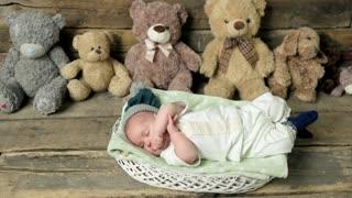 Sleepy baby in a basket. Small child and teddybears.