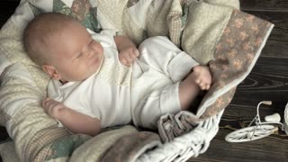 Sleepy baby in basket. Small child lying on blanket. Tired signs in infant.