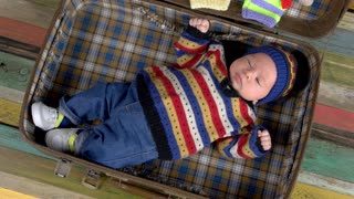 Sleepy baby in suitcase. Little child in knitted sweater. Warm clothes for kids.