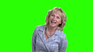Slow motion mature woman is laughing. Middle aged female executive is laughing on chroma key background. Human expressions of joy.