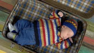 Small child in knitted sweater. Top view of sleeping baby. Trendy clothes for infants.