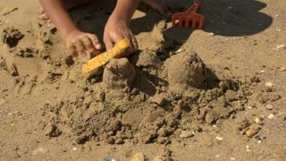 Small child is played in the sand at sea. Boy is digging the sand with a toy shovel. Summer games at the sea. Children on vacation.