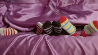 Small feet in colorful socks. Children's feet wearing colorful socks. Purple blanket and striped socks. Wear what you want to.