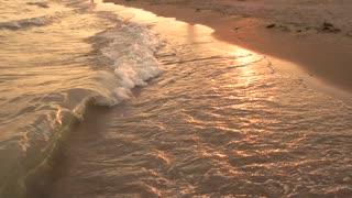 Small waves on the shore. Golden sunset. Beautiful sea coast.