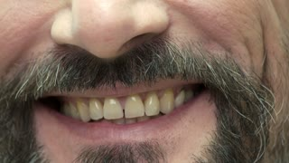 Smile of a bearded man. Smiling mouth close up. Tips for healthy teeth.