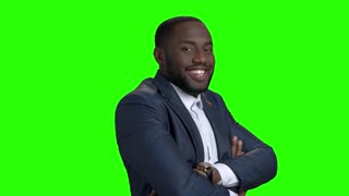 Smiling afro american manager on green screen. Successful afro american entrepreneur crossed arms on chroma key background. People and business concept.