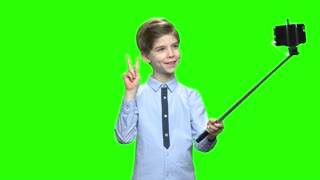 Smiling boy making photos using selfie stick. Making funny face, fooling around, victory gesture. Green hromakey background for keying.