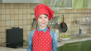 Smiling boy with kitchen utensils. Happy kid in chef uniform. How to make cooking fun.