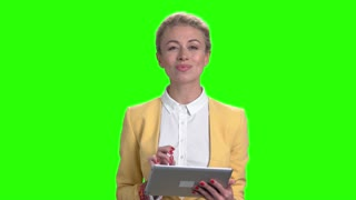 Smiling business lady using digital tablet. Portrait of elegant young female using pc tablet on green screen. People, technology, lifestyle.